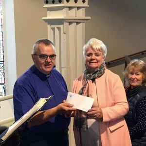 Anna Monahan presents Fr. Tom Ryan with a cheque for €1000.00 for the painting of the cathedral from Ennis Cathedral choir